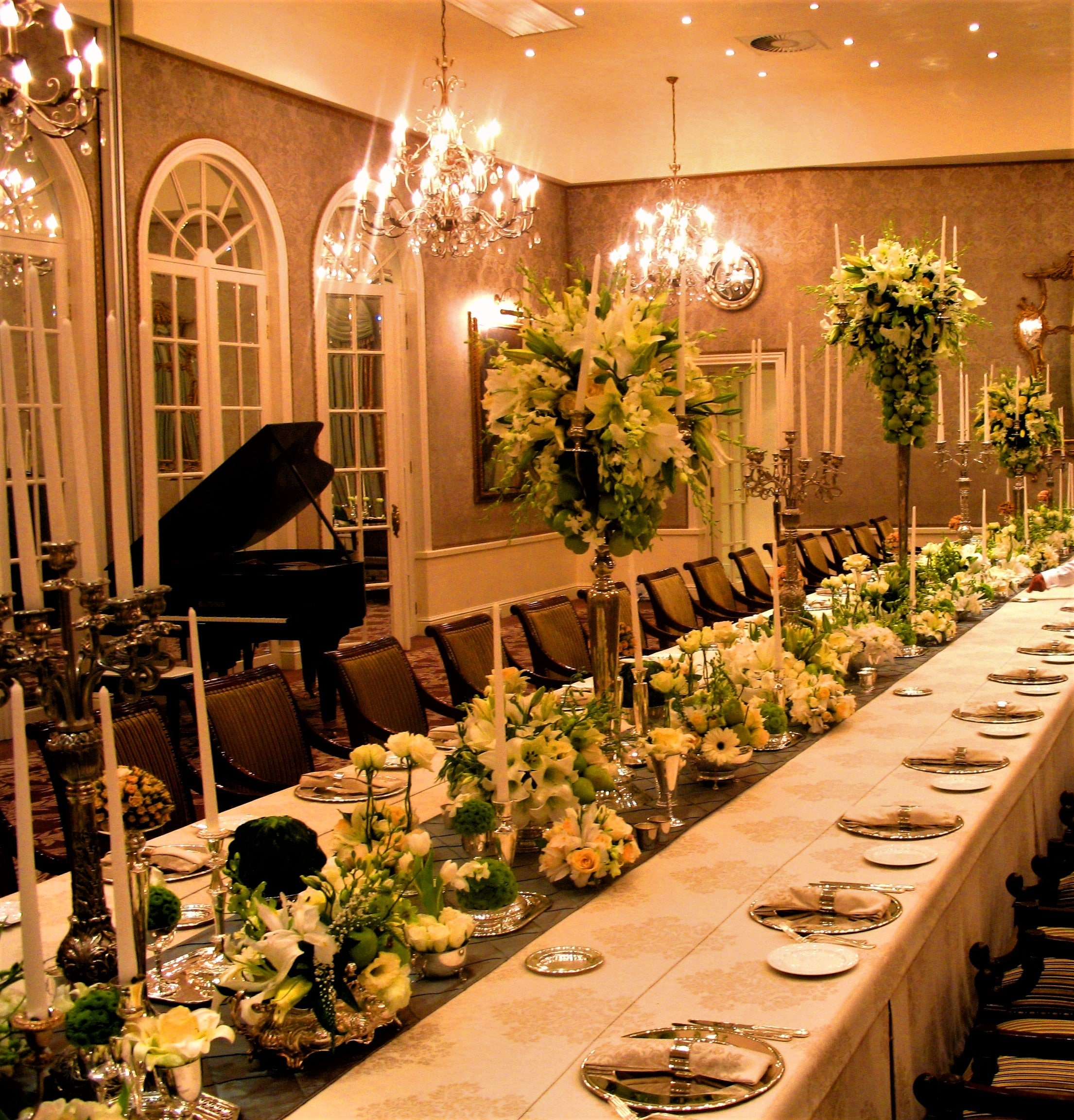 Bold flower table centre piece in silver containers and silver candelabra by Franz Grabe Flowers